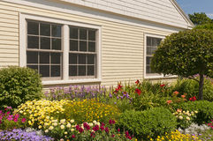 Landscaped house flowerbeds. Landscaped country house with landscaped  flower garden or flowerbed Stock Photo
