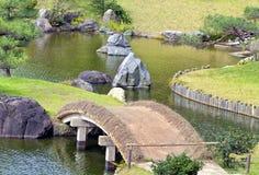 Landscaped oriental garden with bridge rocks in water Stock Image