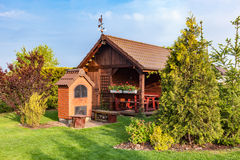Landscaped summer garden with barbecue and wooden summerhouse Royalty Free Stock Images
