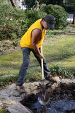 Landscaper. Digging a pond with a shovel Stock Photo