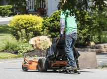 Landscaper riding behind lawnmower on skateboard. A landscaper is getting to another job by riding behind his lawnmower with a skateboard on the road royalty free stock image