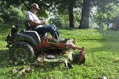 Landscaper on riding lawn mower Stock Photo