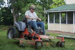 Landscaper on riding lawn mower. Landscaper cutting grass on riding lawn mower Stock Photo