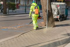 Landscaper worker cleaning foot way in park from dead leaves. Using electric powered Leaf Blower.  royalty free stock photo