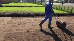 Landscapermannen använder rullen för att hårdna jordjord, når han har kärnat ur gräsmatta Handheld stock video