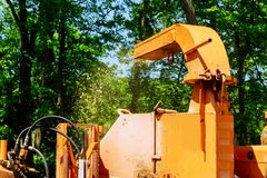 Landscapers using chipper machine to remove and haul chainsaw tree branches. Landscapers using chipper machine to remove and wood Chipper in Action chainsaw tree stock photo