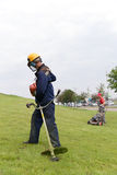 Landscapers workers starting gas trimmer and lawn mower royalty free stock photo