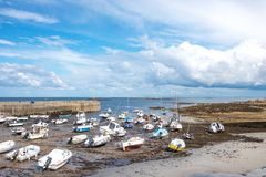 Landscapes and architectures of Brittany. Portivy, France - August 9, 2017: Boats during the low tide in the harbor near the village Stock Images