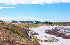 Landscapes and architectures of Brittany. Portivy, France, a beach near the harbor with traditional houses in the background Royalty Free Stock Photos