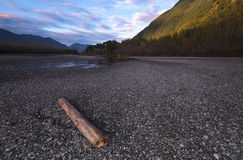 Landscapes. Standing on the shores of the Fraser River the sun sets illuminating the walls of the nearby mountains.  Fraser Valley, BC, Canada Royalty Free Stock Photos