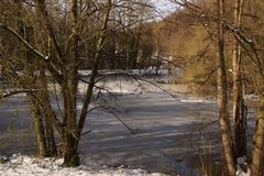 Landscapes wintry - Pond of the mute in a French city which is called Elancourt. Some snow on the ground around trees. He it also some sheets leaves covered stock photography