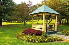 Landscaping around gazebo. Landscaping and flowers around a yellow gazebo with green trim in a park Stock Images