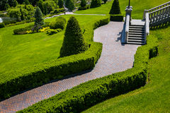 Landscaping in the garden. The path in the garden.Beautiful back. Yard landscape design,Some flowers and nicely trimmed bushes on the leveled front yard Royalty Free Stock Photos