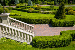 Landscaping in the garden. The path in the garden.Beautiful back. Yard landscape design,Some flowers and nicely trimmed bushes on the leveled front yard Stock Photos