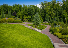 Landscaping in the garden. The path in the garden.Beautiful back. Yard landscape design,Some flowers and nicely trimmed bushes on the leveled front yard Royalty Free Stock Images