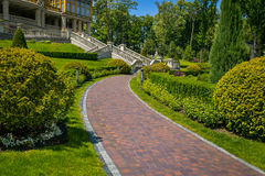 Landscaping in the garden. The path in the garden.Beautiful back. Yard landscape design,Some flowers and nicely trimmed bushes on the leveled front yard Stock Photography