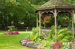 Landscaping gazebo in park. Landscaping around a gazebo with hanging flower baskets in a quiet park stock image