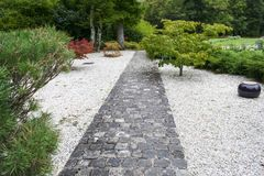 Landscaping, good work of professional landscaper. Stone paved path lined with pebbles surrounded by shrubs, path leading to the garden with flowers and Royalty Free Stock Photo