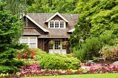 Landscaping log cabin. A view of a small log cottage secluded in the woods with colorful flower landscaping Stock Photo