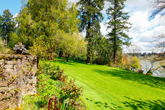 Landscaping near lake with large green lawn and rock wall. Stock Image