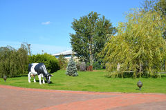 Landscaping with a sculpture of the grazed cow Royalty Free Stock Photos