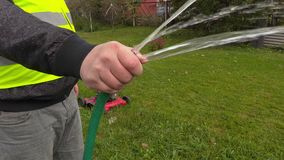 Landscaping worker with with water hose stock footage