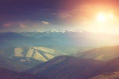 Landschaft in den Bergen: schneebedeckte Oberteile und Frühlingstäler Fantastischer Abend, der durch Sonnenlicht glüht Stockfotografie