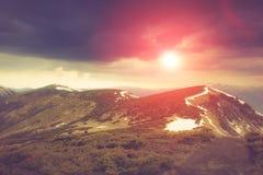 Landschaft in den Bergen: schneebedeckte Oberteile und Frühlingstäler Fantastischer Abend, der durch Sonnenlicht glüht Stockbilder