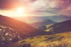 Landschaft in den Bergen: schneebedeckte Oberteile und Frühlingstäler Fantastischer Abend, der durch Sonnenlicht glüht Stockbild
