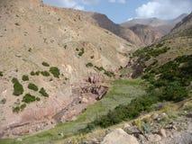 Landschaft der Berge des Atlasses in Maroc mit einem Fluss mit wenigen wässern Lizenzfreies Stockbild