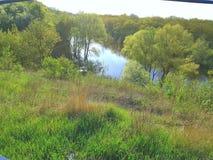 landschaft Der Himmel ist blau Grünes Gras Grüne Bäume Abfall zum Fluss Stockfoto