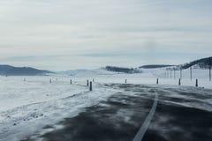 Landschaft der leeren Asphaltstraße biegen durch Schneefeld und -hügel nach links ab Stockfotos