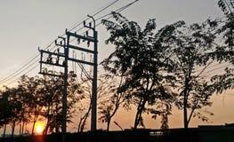 Landschaft der Stromleitung mit Sonnenaufgang Stockfotografie