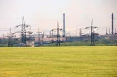 Landschaft des blühenden gelben Feldes und der Stromleitungen Stockfoto
