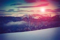 Landschaft des erstaunlichen Abendwinters in den Bergen Fantastischer Abend, der durch Sonnenlicht glüht Stockfotografie