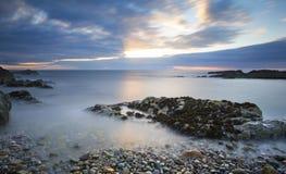 Landschaft des frühen Morgens von Ozean über felsigem Ufer mit glühendem s Lizenzfreies Stockfoto