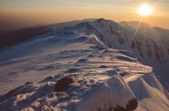 Landschaft des Hochgebirges mit Schnee- und Wolkenatmosphäre und mit sunsut Lizenzfreie Stockbilder