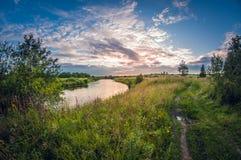 Landschaft des Riverbank bei Sonnenuntergang mit der Sonne über dem Horizont stockbild