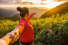 Landschaft des Sonnenuntergangs und der roten Stoffdame führt ihren Liebhaber durch die Hand Lizenzfreie Stockfotos