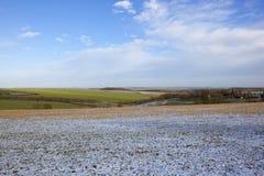 Landschaft des verschneiten Winters mit Ackerland und Dorf Lizenzfreie Stockfotos