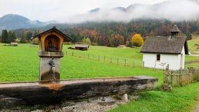 Landschaft eines bayerischen Ackerlands mit einer hölzernen Abflussrinne, Landhäusern u. Scheunen in einer Ranch auf einem nebeli Stockbilder