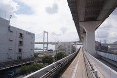 Landschaft eines Zugs, der auf die erhöhte Schiene von Yurikamome-Linie in Odaiba reist Straße unter der Brücke lizenzfreies stockfoto