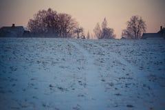 Landschaft im Winter, Schnee auf den Feldern, Häuser und Bäume auf horizont, roter Himmel im Sonnenaufgang Lizenzfreie Stockbilder