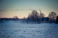 Landschaft im Winter, Schnee auf den Feldern, Häuser und Bäume auf horizont, roter Himmel im Sonnenaufgang Lizenzfreies Stockfoto