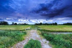 Landschaft mit Ackerland und dunklen Wolken Lizenzfreies Stockbild