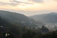 Landschaft mit Dorf, Bergen und Nebel stockfotografie