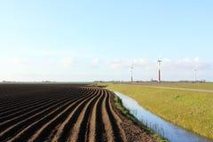 Landschaft mit Dunkelheit gepflogenem Feld und Windkraftanlagen Stockbild