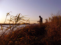 Landschaft mit einem Schattenbildfischer Lizenzfreie Stockfotos