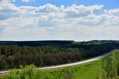 Landschaft mit einem weiten Weg, Wolken und Wald stockbild
