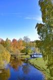Landschaft mit Fluss, Herbstbäumen und Brücke lizenzfreie stockfotos